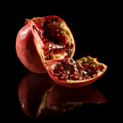 pomegranate, broken fruit isolated on black reflective