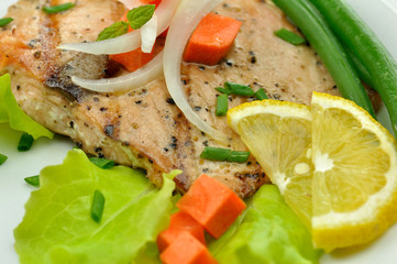 grilled salmon fillet with vegetables and lemon close up