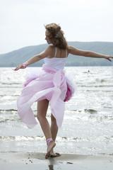 Красивая молодая женщина танцует на пляже
