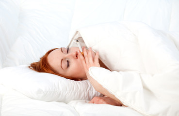 smoking young woman relaxing in white bedding