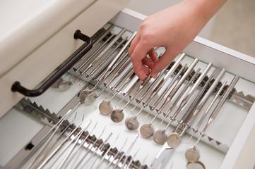 Helferin nimmt einen Zahnarztspiegel aus der Schublade