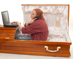phoning woman with laptop sitting in the coffin