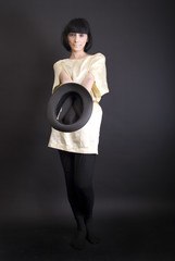 brunette holding an empty hat symbolizing poverty and alms