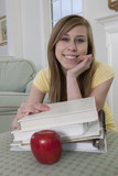 Teen girl smiling with her school books and an apple