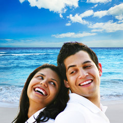 Young couple laughing at the beach