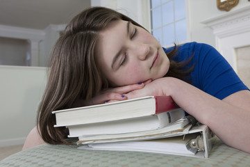 Teenage girl sleeping on her schoolbooks
