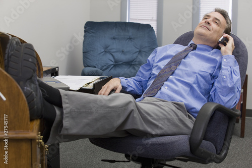 Businessman on the phone with feet in his desk