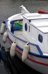 Maritim: weiß-blaues Fischer-Boot mit Bullaugen im Hafen