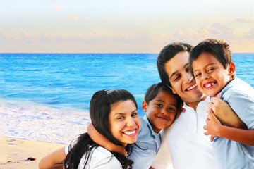 Happy family embracing by the beach