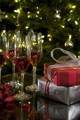 wine glasses and gifts by christmas tree