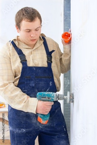 worker with mobile drill wall for installing power socket