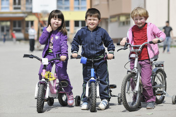 happy childrens group learning to drive bicycle