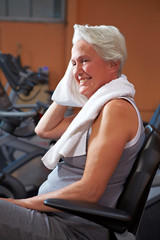 Schwitzende Seniorin im Fitnesscenter