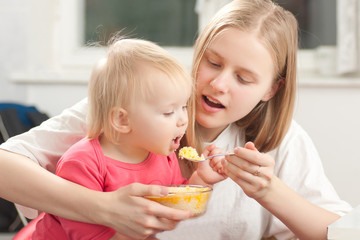 young adorable mother feeding his daughter with porridge
