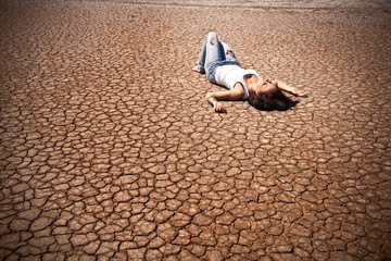 Young woman lying on a deserted land