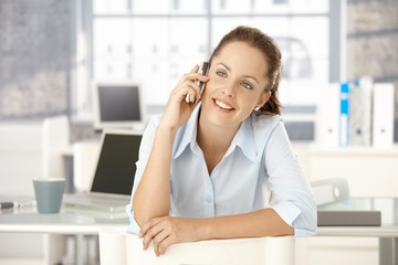 Young female chatting on mobile sitting in office
