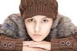 Schöne junge Frau mit Pullover und Mütze blickt ernst