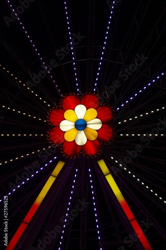 Neon flower in the amusement park by night