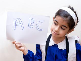 bambina con grembiulie e foglio di carta