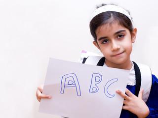 bambina con grembiule e foglio ABC