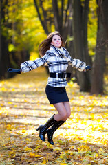Beautiful girl with long hair jumping in a park