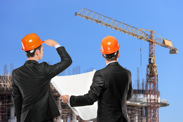 Foremen holding a blueprints and looking at construction site