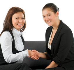 Two businesswoman shake hands