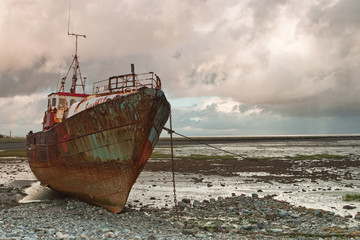 Dead fishing boat on the beach