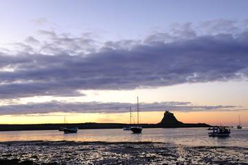 lindisfarne castle (holy island) and harbor at sunrise