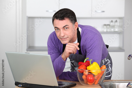 Man in kitchen with laptop computer