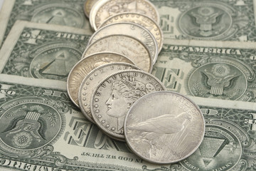 ancient american silver coins on the one dollar bill background