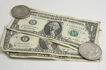 american dollar and silver dollar on the white background