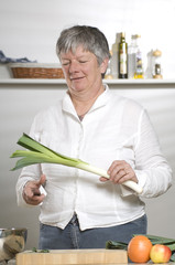 Women is cutting leek in the kitchen