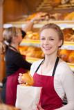 Fototapety lächelnde verkäuferin packt brötchen ein