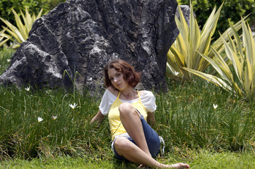 The girl sits on a grass in a garden of the Japanese stones