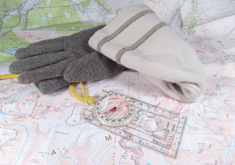 compass, hat and gloves laying on map