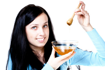 Girl holding honey bowl and honey stick