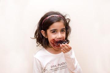 bambina mangia fetta biscottata con marmellata