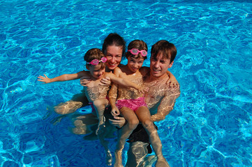 Happy family of four having fun in swimming pool