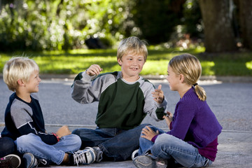 Children sitting and talking together on driveway