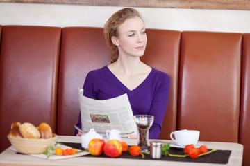junge frau liest zeitung im café