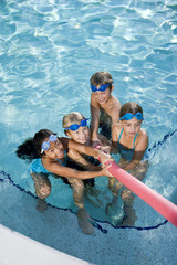 Children playing tug of war in pool