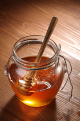 Pot of honey and wooden stick in it.
