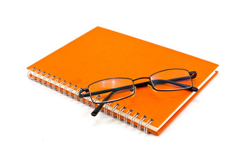orange notebook and sunglasses