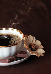 The cup of coffee with chocolate  on brown background