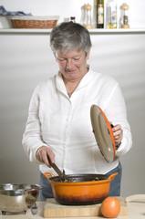 Women is cooking food in a orange pan