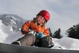 Mädchen mit Snowboard im Vordergrund