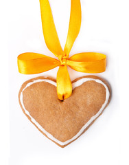 Ginger bread heart and yellow bow isolated on white background