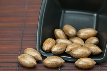 pecans in a bowl on a bamboo mat