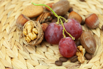 nuts and grapes on a wicker mat